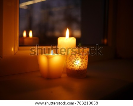 Photo of three lit candles - two paraffin wax candles and one tealight in a glass candle holder with glittery golden ornament, standing on a windowsill late in the evening. #783210058