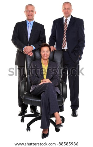 Photo of three mature business people, two businessmen standing behind the businesswoman who is sat on a leather chair, isolated on a white background.