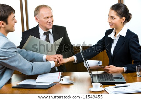 Photo of three partners holding the hands in the office