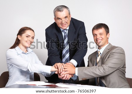 Photo of three partners putting their hands on the top