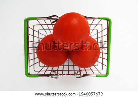 Photo of tomatoes in a small toy shopping basket on a white background. Top view #1546057679