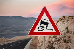 Photo of traffic sign (slippery road warning) with hills nad big mountains on background in Croatia. Black road with warning sign of slippery road and bad surface  at evening on sunset.