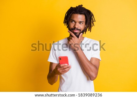 Photo of tricky influencer dark skin guy hold telephone look side sly eyes wear t-shirt isolated yellow color background Stock fotó ©