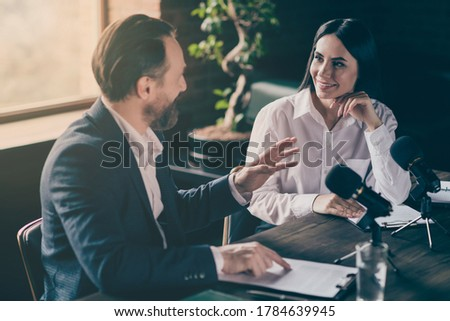 Photo of two business people corporate partners answer journalist press, conference questions speak mic political electoral campaign forum sit modern office indoors