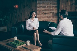 Photo of two business people lady man share news drink hot coffee mug, beverage chatting friendly interview ask answer questions formalwear clothes sit couch modern office indoors