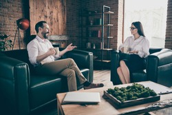 Photo of two business people share corporate news drink hot coffee mug beverage break chatting friendly formalwear clothes sit couch modern office indoors