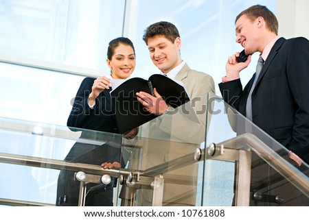 Photo of two businesspeople looking at business plan with smiles in the office with their business partner speaking on the phone near by