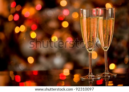 photo of two champagner glasses on glass table with bokeh background