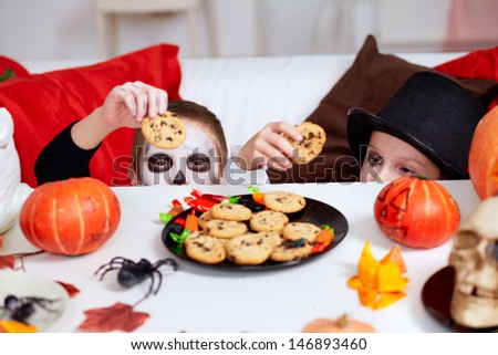 Photo of two eerie boys with cookies looking at camera from under Halloween table