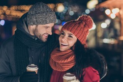 Photo of two funny people pair with hot beverage in hands spending x-mas evening together having best leisure time wearing warm coats knitted caps and scarfs