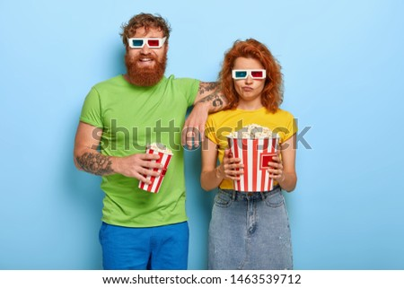 Photo of two girlfriend and boyfriend in love choose appropriate time for visiting cinema, get out of house and enjoy new wider space, cheerful man and bored woman in stereo glasses, eat junk food