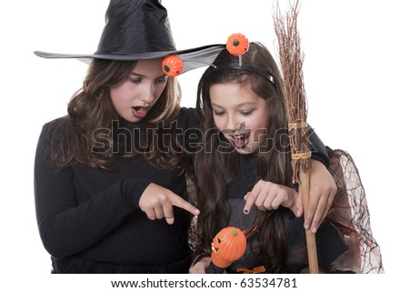 Photo of two girls in halloween costume,  broom and pumpkin looking surprised