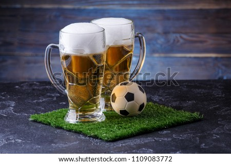 Photo of two glasses of beer, soccer ball on green grass - Shutterstock ID 1109083772
