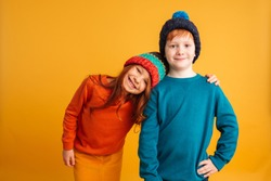 Photo of two happy little children isolated over yellow background wearing warm hats. Looking camera.