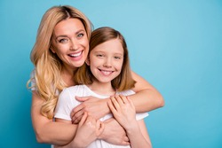 Photo of two people beautiful mommy lady little daughter blonds hugging best friends piggyback holding arms spend time together wear casual white s-shirts isolated blue color background
