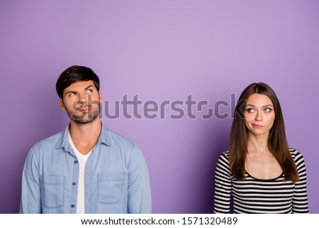 Photo of two people couple looking distrustful up empty space have doubts about new product quality wear stylish casual outfit isolated pastel purple color background