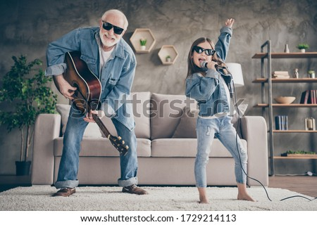 Photo of two people funky grandpa play guitar small nice granddaughter mic singing cool style sun specs denim clothes repetition school concert stay home quarantine living room indoors