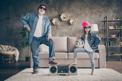Photo of two people grandparent little granddaughter cool vintage style sun specs denim outfit hat house party listen tape player leg on recorder stay home quarantine living room indoors