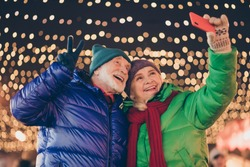 Photo of two people pensioner couple man woman gathering hold telephone, make shoot selfie show v-sign wear coat red scarf headwear x-mas evening street illumination fair outdoors outside