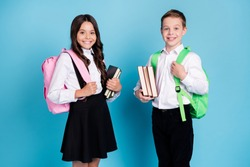 Photo of two small girl boy schoolchildren brother sister classmates hold books walk library study year finishing wear backpack white shirt black pants dress isolated blue color background