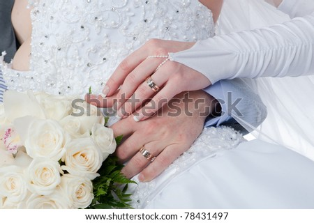 Photo of two tender hands of the groom and the bride with wedding rings and bouquet of white roses close up