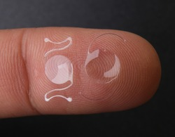 photo of two types of intra ocular lens on finger tip