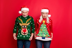 Photo of two upset surprised amazed shocked wife husband people friend taking part in competition showing clothes seasonal jumpers with x-mas decor isolated vibrant background