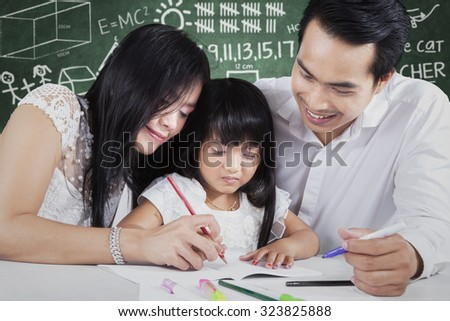 Photo of two young asian teacher teach a female elementary school student studying and write on the book, shot in the classroom