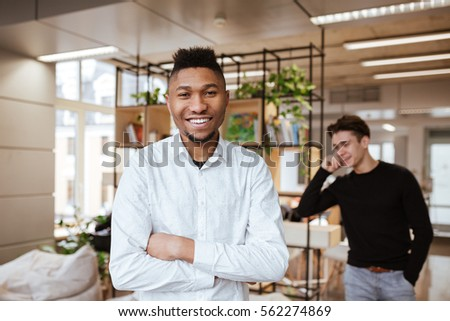 Photo of two young handsome students in library. Caucasian guy talking by phone on background. African boy looking at camera with arms crossed.