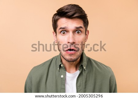 Photo of unhappy upset young man astonished stupor stare isolated on pastel beige color background Foto d'archivio ©