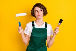Photo of unsure nice brown hair lady hold roller brush wear uniform isolated on yellow background