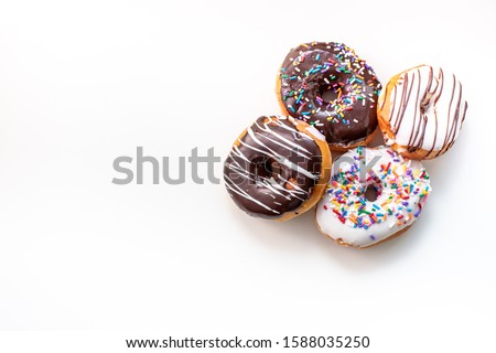 Photo of various donuts on a white table with frozen chocolate, sprinkled and sprinkled.