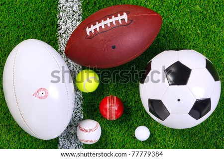Photo of various sports balls on a grass next to the white line shot from above