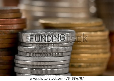 Photo of various stacks and rows of coins with FUNDING concept word imprinted on metal surface