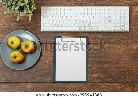 Photo of well organized wooden desk with healthy snacks