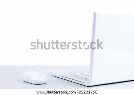 Photo of white cordless laptop with mouse of the same color near by