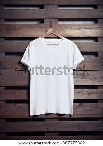 Photo of white tshirt hanging on wood background. Vertical blank mockup #387275362