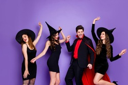 Photo of witch ladies and warlock guy friendship chilling at halloween party dancing wear black dresses hats and vampire coat isolated purple color background