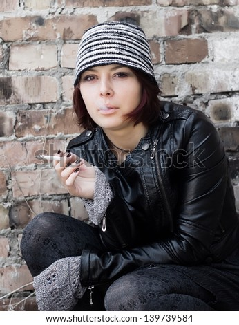 Photo of woman in retro grunge style smoking a cigarette - stock photo