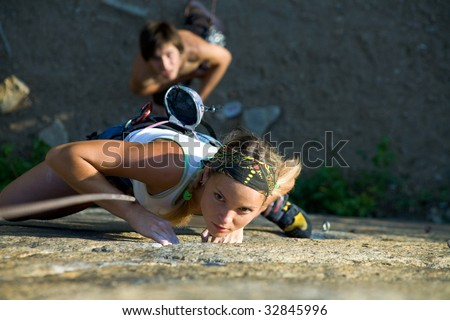 Photo of woman in sport wear climbing up mountain