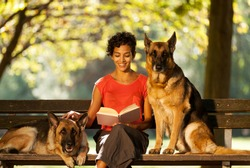 Photo of woman sitting on a bench with two german shepherds