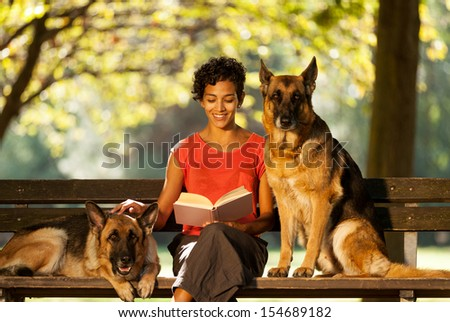Photo of woman sitting on a bench with two german shepherds #154689182