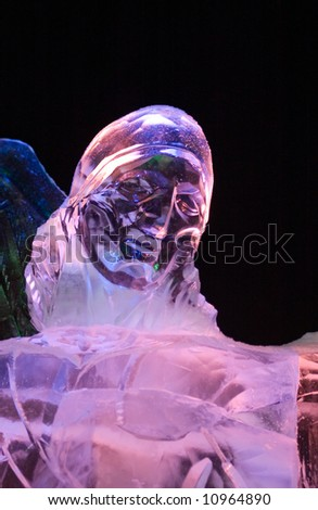 Photo of woman statue made from ice and lightened with different colored lamps