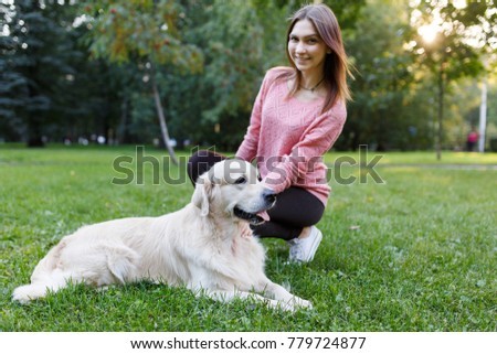 Shutterstock Photo of woman with dog lying on lawn in summer park