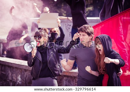 Photo of woman with megaphone and protesting couple