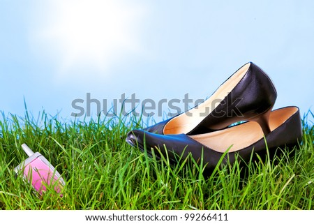 Photo of womens high heel shoes and a mobile phone on grass against a bright blue sky with sunshine. - stock photo