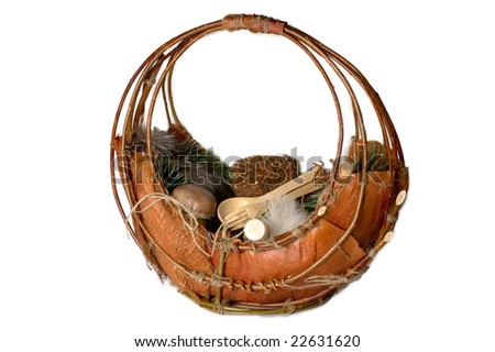 Photo of wooden basket with toy hedgehog and fir branch and wooden kitchenware and wine bottle in it isolated on white background - stock photo
