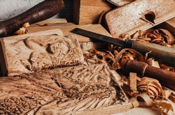 Photo of wooden old fashioned planes with carving chisels laying on workbench table with dragon and woman goddess bas-relief wooden sculpture.
