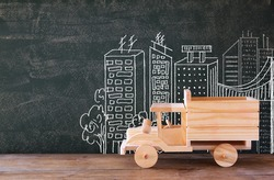 photo of wooden toy truck in front of chalkboard with city illustration.