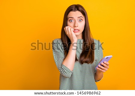 Photo of worried concerned girlfriend seeing her phone screen cracked and shattered to pieces while isolated with yellow background